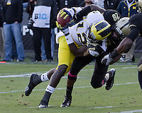 Michigan wide receiver Devin Gardner scores on a 23-yard touchdown catch despite the efforts of Purdue cornerback Josh Johnson (28). The Michigan Wolverines defeated the Purdue Boilermakers 44-13 on October 6, 2012 at Ross-Ade Stadium in West Lafayette, Indiana.