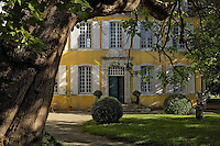 The yellow ochre facade of this 18th century French manor house is bathed in afternoon sunshine