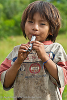 Machiguenga boy playing on a self-made flute, Tayakome native communitiy, lowland tropical rainforest, Manu National Park, Madre de Dios, Peru.
