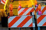Striped construction barriers guard the entrance to a building site.