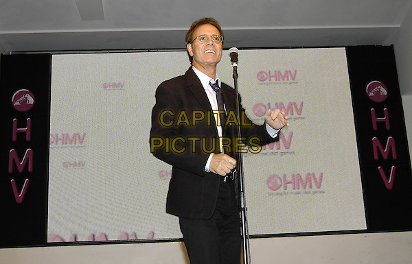 "CLIFF RICHARD.At HMV Oxford Circus, London..Launch of his new single ""What Car"" with a free performance and signing..May 9th, 2005.half length live gig glasses black suit.www.capitalpictures.com.sales@capitalpictures.com.©Capital Pictures"