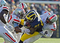 Ohio State Buckeyes linebacker Joshua Perry (37), Ohio State Buckeyes cornerback Bradley Roby (1) and Ohio State Buckeyes line backer Ryan Shazier (2) come together to tackle Michigan Wolverines running back Derrick Green (27) in the 3rd quarter of their college football game at Michigan Stadium in Ann Arbor, Michigan on November 30, 2013.  (Dispatch photo by Kyle Robertson)