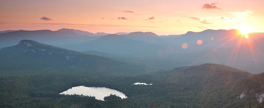 The setting sun over remote Sawyer Pond in the Pemigewasset Wilderness region of New Hampshires White Mountains.