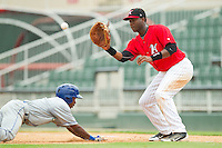 Terrance Gore (6) of the Lexington Legends dives back to first base as Keon Barnum (35) of the Kannapolis Intimidators waits for the pick-off throw at CMC-Northeast Stadium on July 31, 2013 in Kannapolis, North Carolina.  The Intimidators defeated the Legends 3-2.  (Brian Westerholt/Four Seam Images)