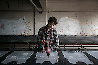 February 13, 2016: A Syrian refugee worker uses a heater as he works in the print process of shirts at a print factory in Gaziantep. The factory is owned by Sherif Khalil (not pictured), a Syrian Kurdish businessman that fled into Turkey during the war in the neighbouring country and currently owns the factory that also gives job to other refugees from Syria.