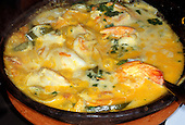 Recife, Brazil. Muqueca de Peixe fish stew with prawns in an earthenware dish.