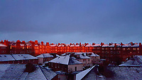 A row of townhouses in Polwarth Gardens are illuminated by the setting sun sets over roof tops in Edinburgh, Scotland, UK. Wednesday 04 April 2018