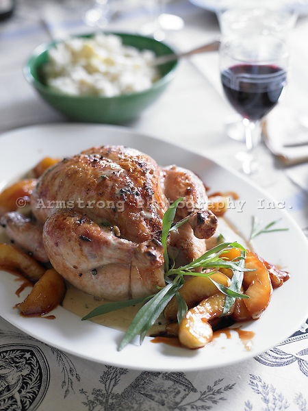 Whole roasted chicken with baked apple slices, fresh herbs. Glass of red wine and bowl of mashed potatoes in background.