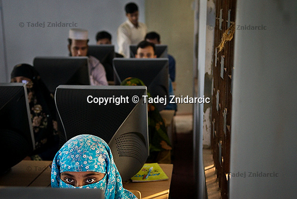 A young woman works on a computer during a computer literacy lesson at the Shidhulai's regional office. The rural areas of Bangladesh are very traditional and a lot of women are veiled. (Photo by Tadej Znidarcic)