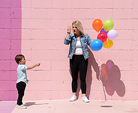 Roman Smolinski, 3, laughs Thursday, May 21, 2020, as he holds a balloon alongside his mother, Ally Smolinski of Rogers, while taking family photographs in front of the Maude Wall at Maude Boutique in Fayetteville. The clothing store invites patrons to use their multicolored back wall for photographs. Visit nwaonline.com/200522Daily/ for today's photo gallery.<br /> (NWA Democrat-Gazette/Andy Shupe)
