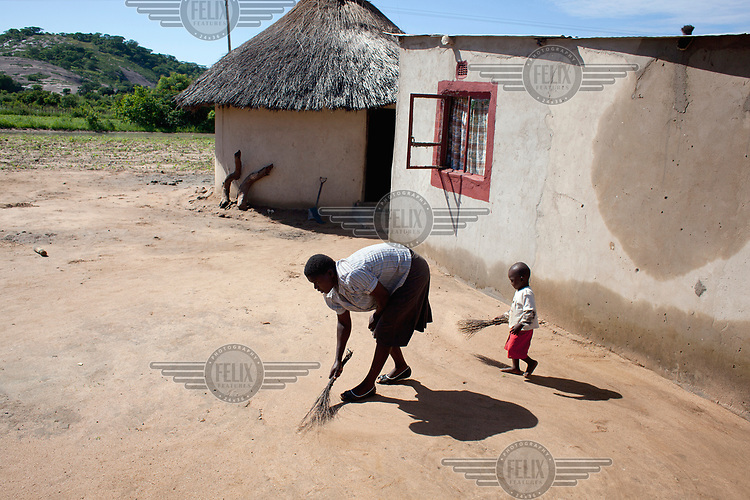 Preserve Dewa (26) with help from three year old Wisdom, sweeps the ground outside her home.