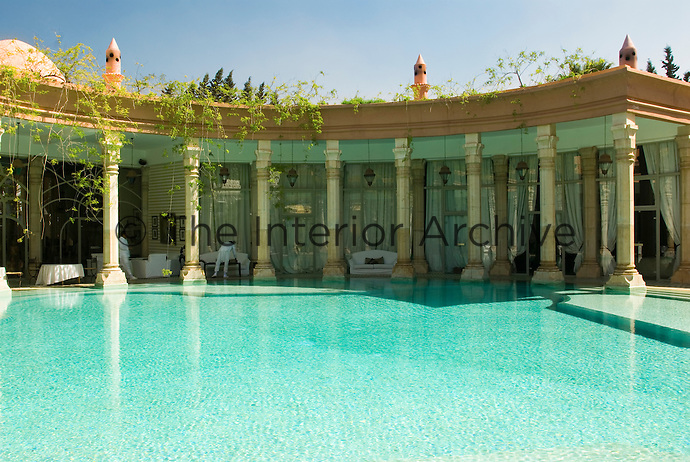 A curved colonnade framing the swimming pool under which guests can rest at Le Palais Rhoul
