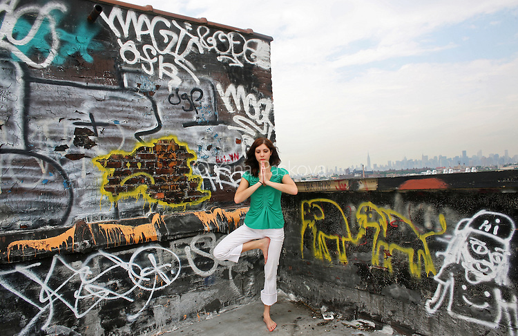Erin Laubenheimer poses for a portrait in a yoga pose on the rooftop of her apartment building in the Bushwick neighborhood of Brooklyn, New York, on Friday, June 26, 2009.  Laubenheimer is an artist looking for work, who does yoga in her spare time to reduce stress.  (Photo by Yana Paskova for The New York Times)
