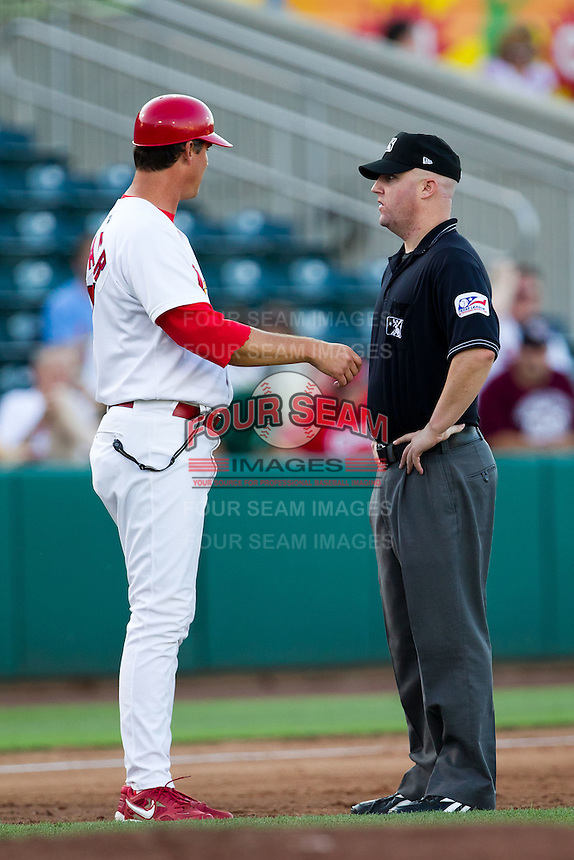 """Manager Ron Warner (57) of the Springfield Cardinals argues with third base umpire Ryan Blakney about a Tulsa player called """"safe"""" during a game against the Tulsa Drillers at Hammons Field on July 18, 2011 in Springfield, Missouri. (David Welker / Four Seam Images)"""