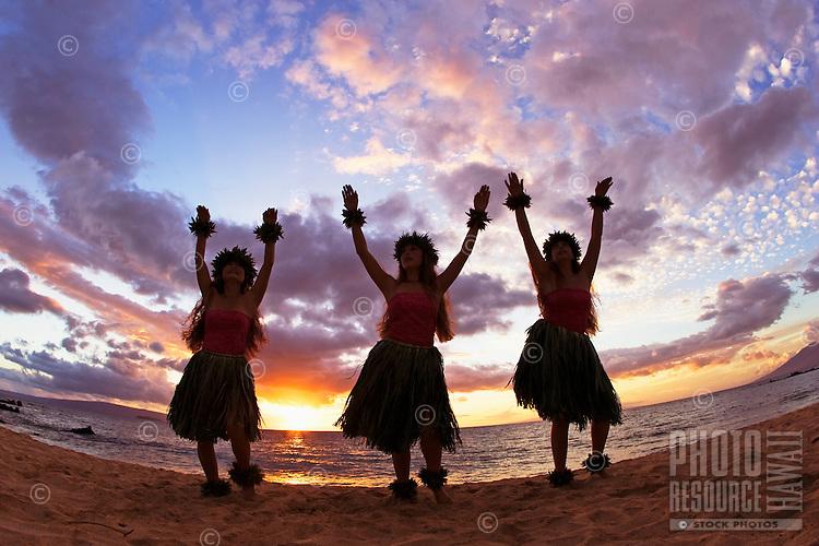 Three hula dancers at sunset at Palauea Beach, Maui, Hawaii, USA.
