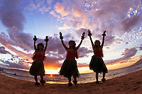 Three hula dancers at sunset at Palauea Beach, Maui, Hawaii, USA.