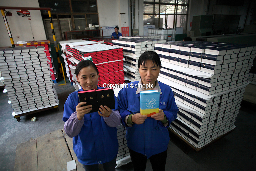 Workers at Amity Printing Co in Nanjing, 03 Dec 2007, hold copies of the bible. The factory is a joint venture with the United Bible Society that produces millions of bibles annually.<br />