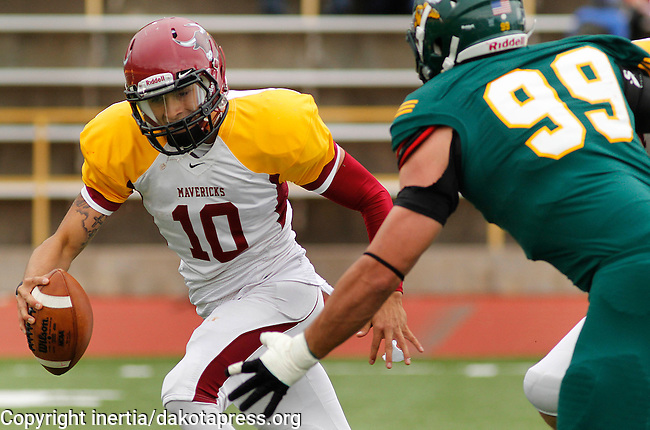 OCTOBER 4, 2014 -- Colorado Mesa quarterback Andrew Cota #10 tries to evade Sam Prentner #99 of Black Hills State during their Rocky Mountain Athletic Conference game Saturday at Lyle Hare Stadium in Spearfish, S.D.  (Photo by Dick Carlson/Inertia)