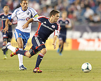 New England Revolution midfielder Kelyn Rowe (11) on the attack. In a Major League Soccer (MLS) match, Montreal Impact (white/blue) defeated the New England Revolution (dark blue), 4-2, at Gillette Stadium on September 8, 2013.