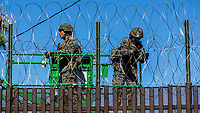 "MEXICALI,  MEXICO - November 26. US Army soldiers are seen from the mexican side fortifying US-Mexico border fence with barbed wire  on November 26, 2018 in Mexicali, Mexico.<br /> The U.S. government said it was starting work to ""harden"" the border crossing  Mexico, to prepare for the arrival of a migrant caravan leapfrogging its way across western Mexico. For the Trump administration and those who support the president's hard-line stance on illegal immigration, the chaos illustrated what they long have feared. For others, the images of the Border Patrol using tear gas on a group of migrants that included children were deeply disturbing (Photo by Luis Boza/VIEWpress)"