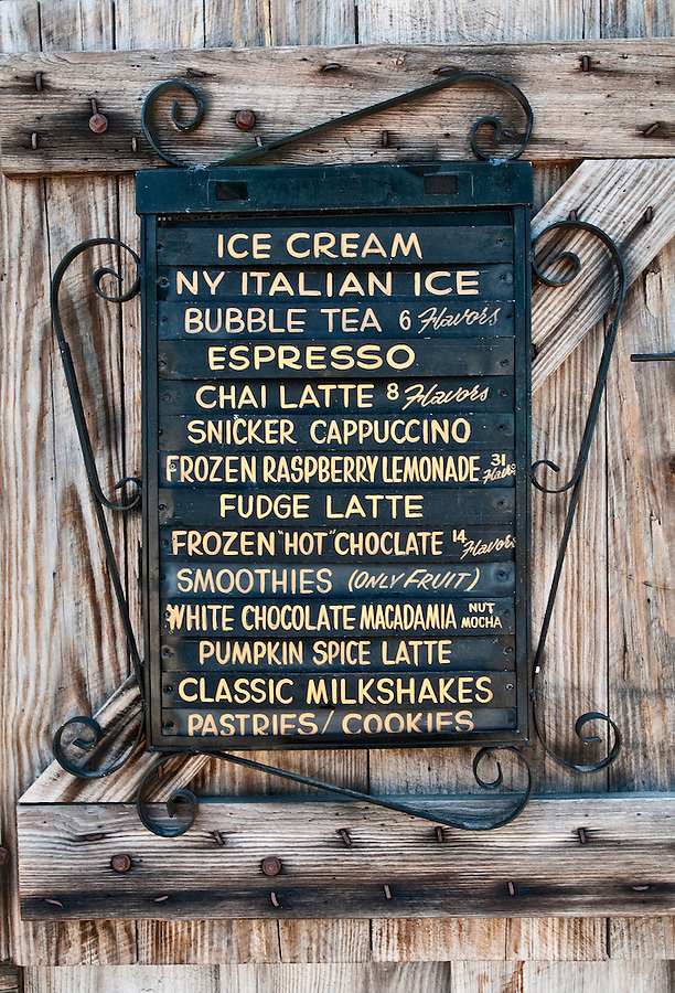 Old wooden sign annoucing coffes and ice cream in a shop.