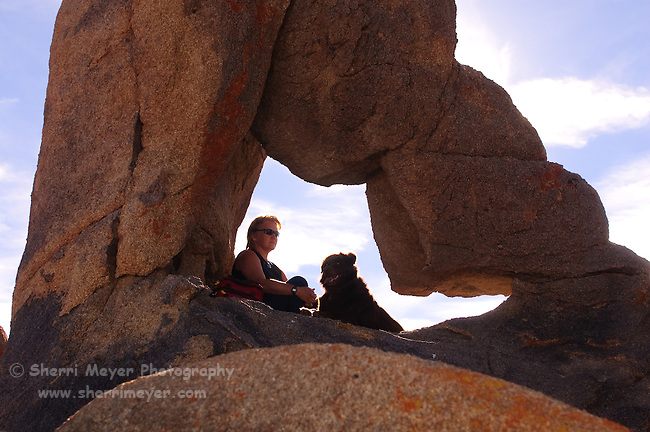 Woman and dog sitting in an arch, Alabama Hills, Lone Pine, California