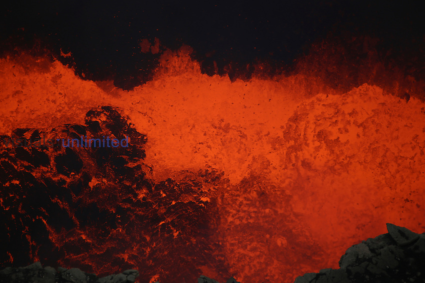 Lava lake with bursting lava bubble in bottom of Santiago Crater of erupting Masaya Volcano, Nicaragua