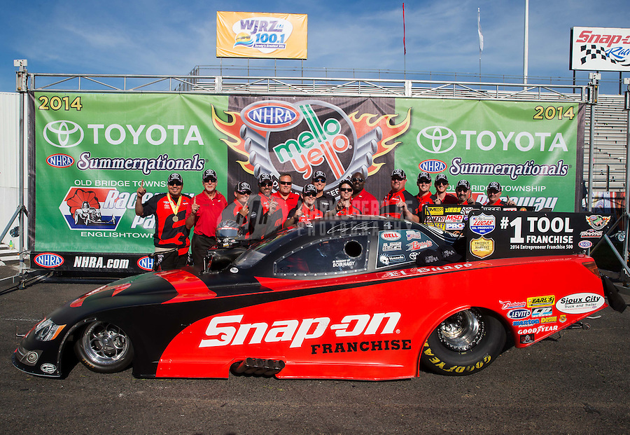 Jun. 1, 2014; Englishtown, NJ, USA; NHRA funny car driver Cruz Pedregon  celebrates with his crew after winning the Summernationals at Raceway Park. Mandatory Credit: Mark J. Rebilas-