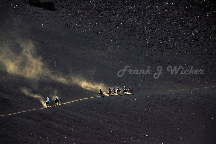 Dust from horseback riders highlighted by golden sun in the crater of HALEAKALA NATIONAL PARK  on Maui in Hawaii USA