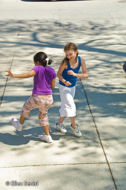 MR / Schenectady, NY. Elmer Avenue School (urban public elementary school). 3rd Grade. Girls dance together outside on sidewalk. Girl left: 8, African American & Puerto-Rican American; girl right: 8. MR: Fra6, Mit10. ID: AH-FRD. © Ellen Senisi