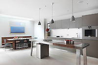 The minimal style open-plan kitchen/dining room, furnished with a stainless steel work bench lit with pendant lights; grey units and pale wood flooring