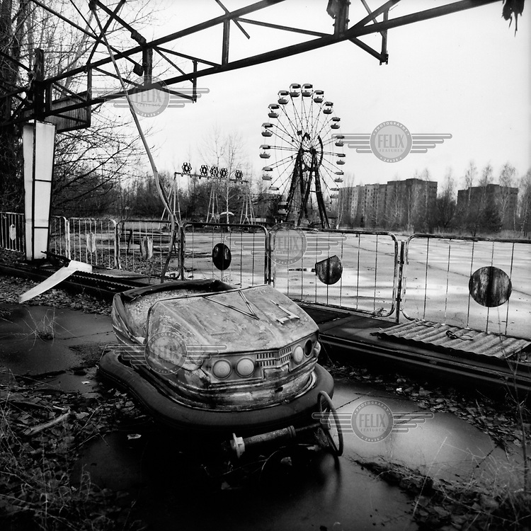 A fairground ride in Pripyat the abandoned town which was built to house workers at the Chernobyl nuclear power plant. On 26th April 1986, a reactor at the Chernobyl nuclear power plant suffered a series of explosions which led to a nuclear meltdown. 28 people died from immediate radiation exposure from smoke released in the blast. The energy released dragged a plume of uranium dioxide and radioactive particles and gases high into the atmosphere which were scattered over a wide area by eddying atmospheric winds. A 30km evacuation zone was created around the reactor, displacing 135,000 local residents, many of whom have since returned to the region. Millions lived and continue to live in the contaminated area, also known as the zone of alienation.