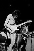 "Chicago, Illinois<br /> July 23, 1975<br /> USA<br /> <br /> Guitarist Ronnie Wood of the Rolling Stones performs live at Chicago Stadium during the band's ""Rolling Stones Tour of the Americas '75"".<br /> <br /> This was the Stones first tour with new guitarist Ronnie Wood, after Mick Taylor left the band. The Stones, with their usual act freshly aided by theatrical stage props  including a giant inflatable phallus (nicknamed 'Tired Grandfather' by the band, since it sometimes malfunctioned) and, at the Chicago shows, an unfolding lotus flower-shaped stage that Charlie Watts had conceived.<br /> <br /> The band was composed of  Mick Jagger - vocals, guitar, harmonica, Keith Richards - guitar, vocals, Bill Wyman - bass guitar, and Charlie Watts - drums, percussion. <br /> <br /> Additional musicians included: Ronnie Wood - guitar, backing vocals, Ian Stewart - piano, Billy Preston - keyboards, vocals and Ollie Brown - percussion."