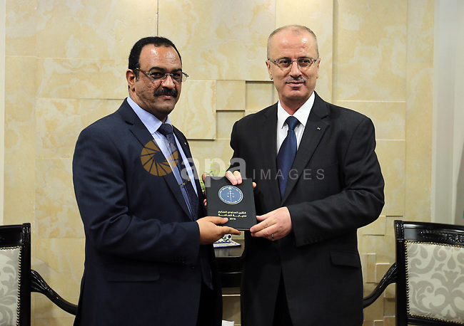 Palestinian Prime Minister Rami Hamdallah receive the Seven th Annual Report of the Public Prosecution for 2016 in the West Bank city of Ramallah on April 17, 2017. Photo by Prime Minister Office