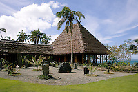 A gravel garden of rocks and standing stones nurtures some young palm trees in the lee of a traditional thatched pavilion