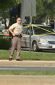 Aspen Hill, MD - October 3, 2002 -- An unidentified Montgomery County (MD) police officer stands guard at the Aspen Hill Mobil where 2 persons were shot this morning, 3 October, 2002 in Aspen Hill, MD.  A blood stain from one of the victims is clearly visible on the side of the car.<br /> Credit: Ron Sachs / CNP<br /> (RESTRICTION: NO New York or New Jersey Newspapers or newspapers within a 75 mile radius of New York City)