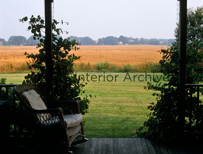 Framed by climbing Honeysuckle a wicker rocking chair looks out from the porch over a field of ripening wheat