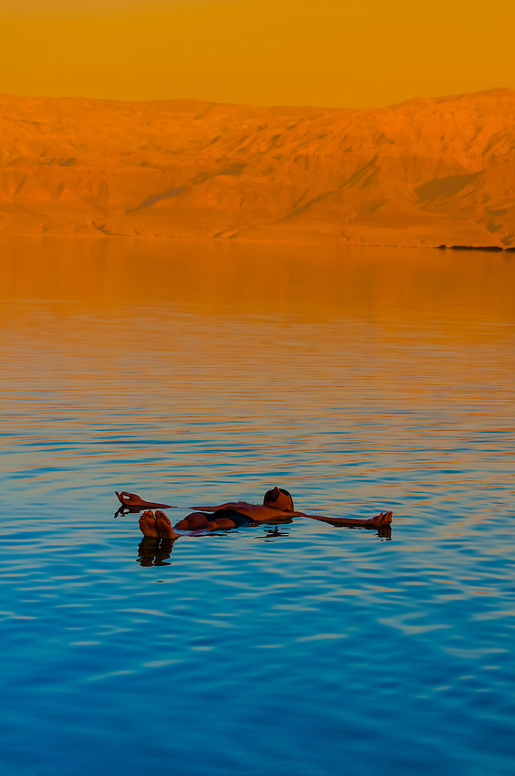 Tourists enjoying the waters of the Dead Sea (with Jordan in the background) at the Leonardo Plaza Dead Sea Hotel, Israel.