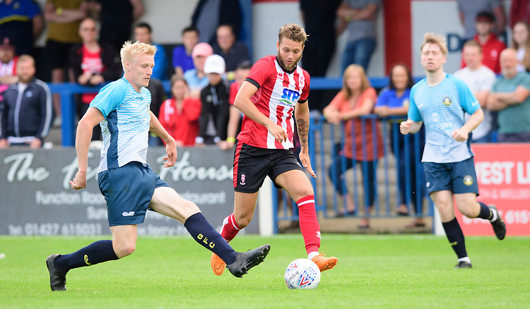 Gainsborough Trinity's trialist under pressure from Lincoln City's Jorge Grant<br /> <br /> Photographer Chris Vaughan/CameraSport<br /> <br /> Football Pre-Season Friendly (Community Festival of Lincolnshire) - Gainsborough Trinity v Lincoln City - Saturday 6th July 2019 - The Martin & Co Arena - Gainsborough<br /> <br /> World Copyright © 2018 CameraSport. All rights reserved. 43 Linden Ave. Countesthorpe. Leicester. England. LE8 5PG - Tel: +44 (0) 116 277 4147 - admin@camerasport.com - www.camerasport.com