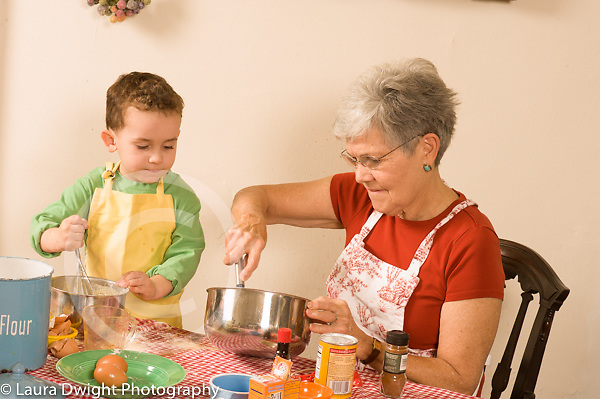 3 year old boy cooking baking activity with grandmother  modeling imitation stirring his own bowl as grandmother stirs hers horizontal looking and observing how she stirs