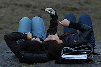 Women check a mobile in Central Park during the fist day of Spring in New York City. March 20, 2014. Photo by Eduardo Munoz/VIEW