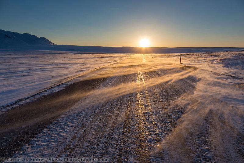 High winds blow snow across the James Dalton Highway at sunset, Arctic, Alaska.