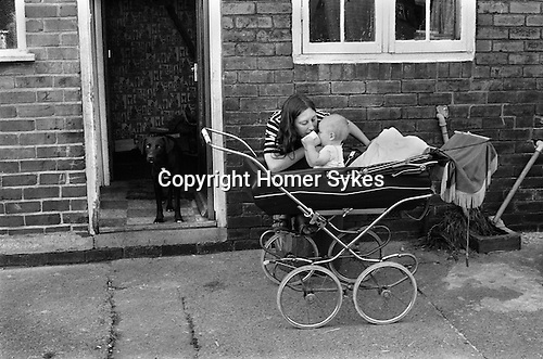 Mrs Carol Blackhouse and baby Craig in pram. Snoopy in the doorway.  Northfield estate. South Kirkby.  South Kirkby colliery Yorkshire England. 1979. This is the back of their home.