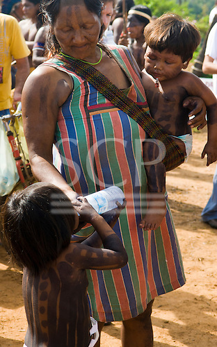 "Altamira, Brazil. ""Xingu Vivo Para Sempre"" protest meeting about the proposed Belo Monte hydroeletric dam and other dams on the Xingu river and its tributaries. A Kayapo Indian mother gives her daughter a drink of mineral water from a plastic bottle."