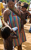 """Altamira, Brazil. """"Xingu Vivo Para Sempre"""" protest meeting about the proposed Belo Monte hydroeletric dam and other dams on the Xingu river and its tributaries. A Kayapo Indian mother gives her daughter a drink of mineral water from a plastic bottle."""