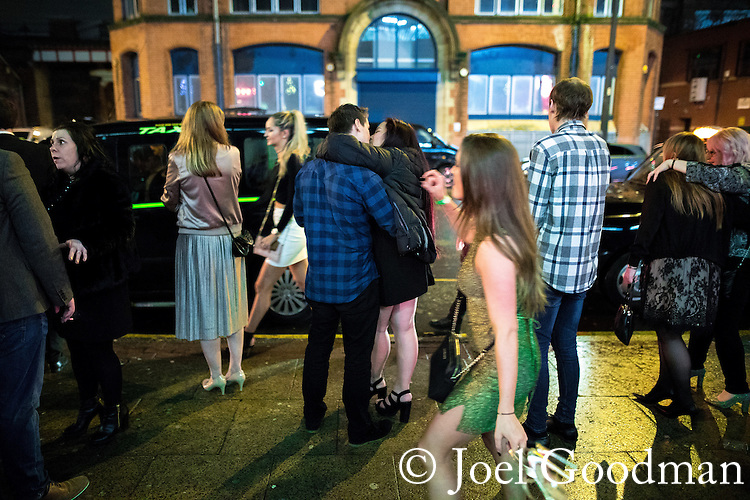 "© Joel Goodman - 07973 332324 . 17/12/2016 . Manchester , UK . A couple embrace as they queue for a taxi , on Deansgate Locks . Revellers out in Manchester City Centre overnight during "" Mad Friday "" , named for being one of the busiest nights of the year for the emergency services in the UK . Photo credit : Joel Goodman"