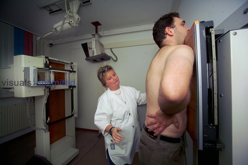 Male patient having a chest X-ray by a female pulmonologist