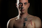 "Justin Griffith, 29, is a sergeant in the US Army and an atheist, to which his ""A"" tattoo alludes.  Recently named as Military Director of American Atheists, Griffith is trying to get atheists more respect within the military and has organized a pro-atheism event, Rock Beyond Belief, at Fort Bragg, where he is stationed.  Griffith was photographed at his Fayetteville, NC, home on Sunday, March 11, 2012.  Photo by Ted Richardson"