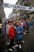Krakow, Poland. Group of school children; Adidas advert; shopping street.