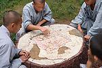 Shaolin martial arts school students playing Xiangqi Chinese chess outside in DengFeng, Zhengzhou, Henan, China 2014